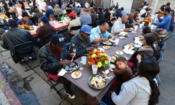 A child rests her head on the table as some homeless people have their lunch at the LA Mission's annual Thanksgiving meal.