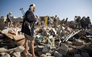 A Houthi Shiite fighter stands guard on Thursday as people search for survivors under the rubble of houses destroyed by Saudi airstrikes near Sanaa Airport