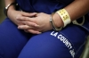 A woman sits handcuffed after arriving at the Los Angeles County women's jail in Lynwood, California.