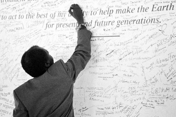 A participant signs the Earth Pledge at the United Nations Conference on Environment and Development, June 1992