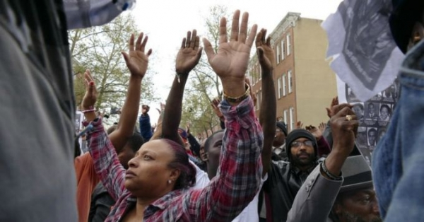 Residents kneel down, raising their hands to the sky behind concrete barriers placed there to expand the barriers of the Western District of the Baltimore Police as marchers take to the streets for another day of protests over the death of local resident Freddie Gray, while in police custody.