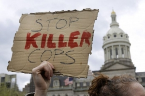 A protestor holds a sign outside of Baltimore's City Hall before a march for Freddie Gray, Thursday, April 23, 2015, in Baltimore. Gray died from spinal injuries about a week after he was arrested and transported in a police van.